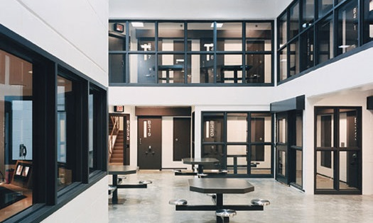 White walls with windows that look over a metal table common area in the Douglas County Jail