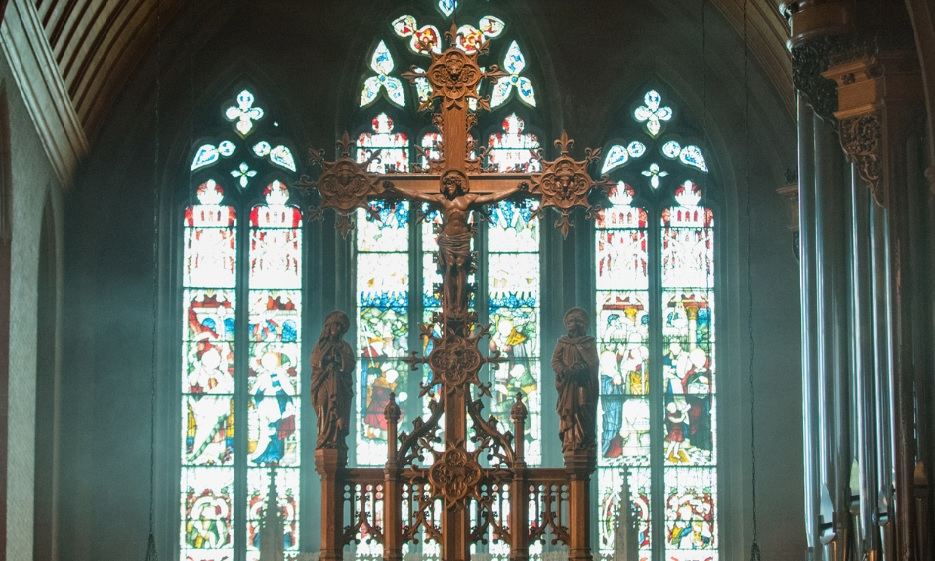A wooden crucifix in front of three stained glass windows.
