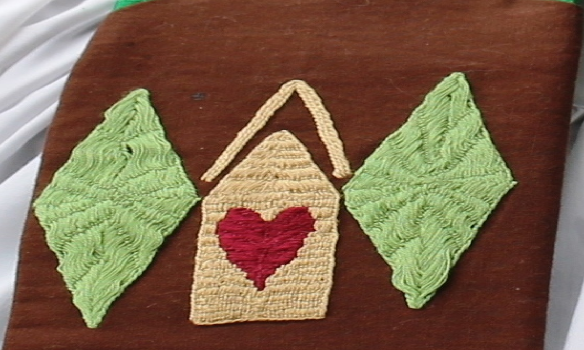 Embroidery of a yellow house with a red heart between two light green diamonds on a brown background.