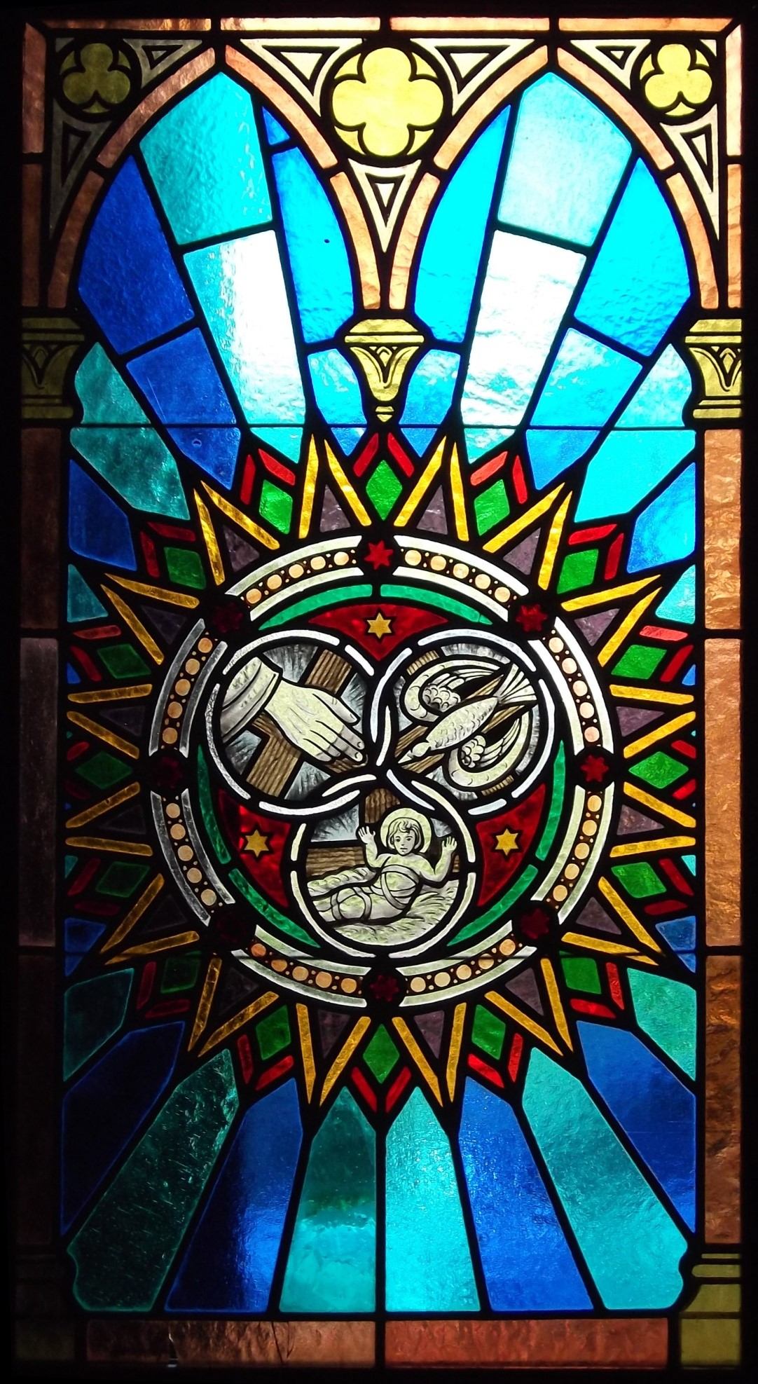 Stained glass window featuring three interlocked circles, with 