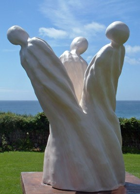 A statue of three armless humanoid figures that are joined together at the base.
